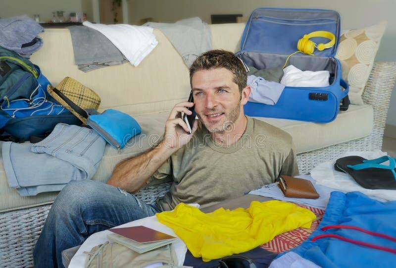Hombre hermoso y feliz joven que habla con el amigo en el teléfono móvil mientras que embala la ropa de organización y cosas de l foto de archivo