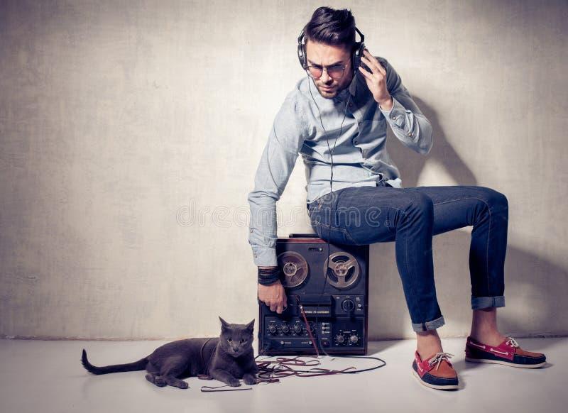Hombre hermoso y gato que escuchan la música en un magnetophone imagenes de archivo