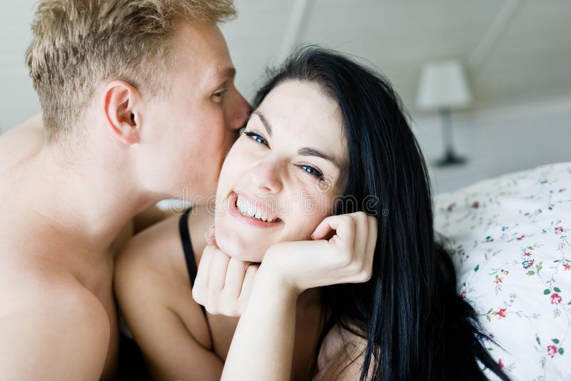 Hombre hermoso y mujer agradable que presentan en la cama - momentos ?ntimos en dormitorio imágenes de archivo libres de regalías
