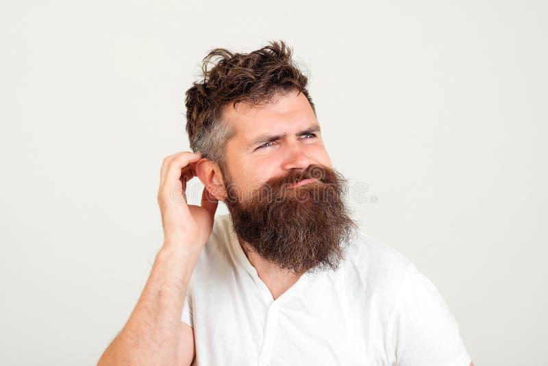 Hombre hipster con barba pensando Un hombre guapo piensa en los planes futuros, siendo un poco confundido Joven barbudo de fondo  foto de archivo