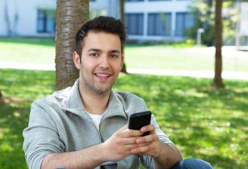 Hombre hispánico afuera en un parque que envía el mensaje imagenes de archivo