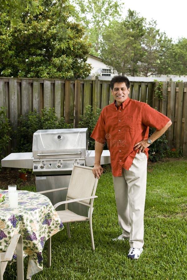 Hombre hispánico al lado de la parrilla del patio trasero fotografía de archivo