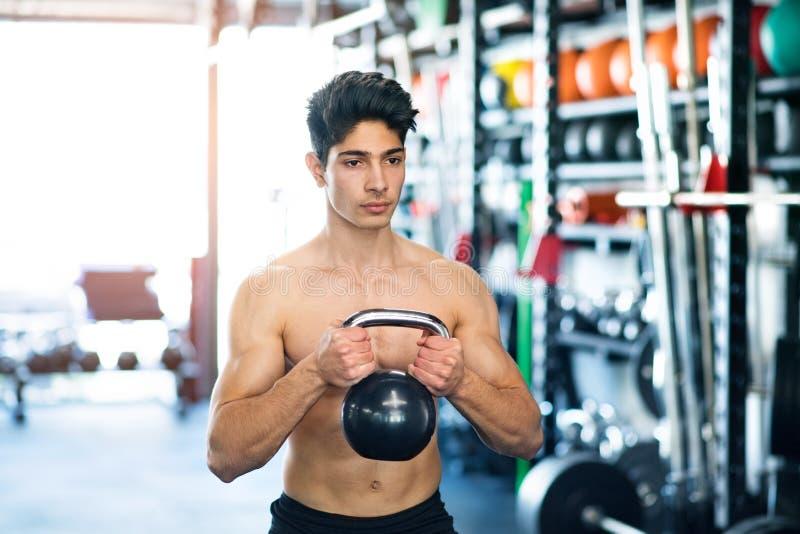 Hombre hispánico apto de los jóvenes en gimnasio que ejercita con el kettlebell fotos de archivo libres de regalías