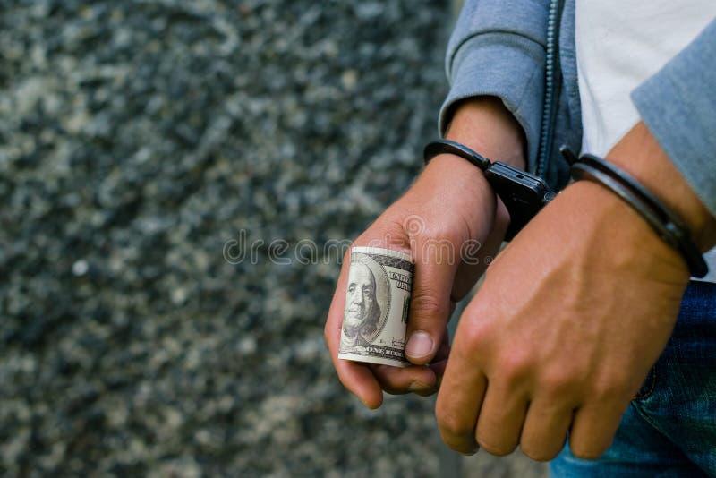 Hombre hispánico arrestado en esposas con el billete de banco del dólar Arreste foto de archivo