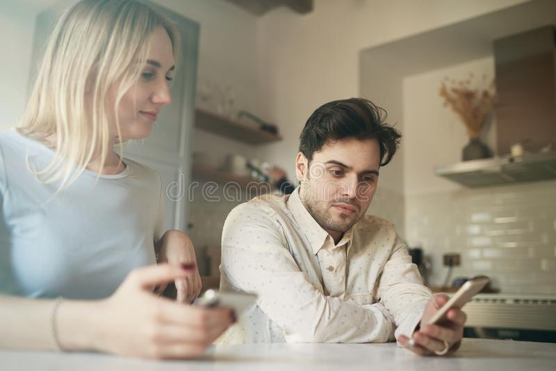 Hombre hispánico atractivo y mujer rubia que usa los teléfonos móviles en casa imagenes de archivo