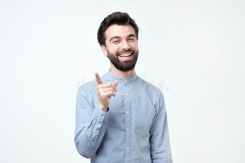 Hombre hispánico barbudo positivo feliz vestido en la camisa azul que señala su dedo índice hacia arriba fotos de archivo libres de regalías