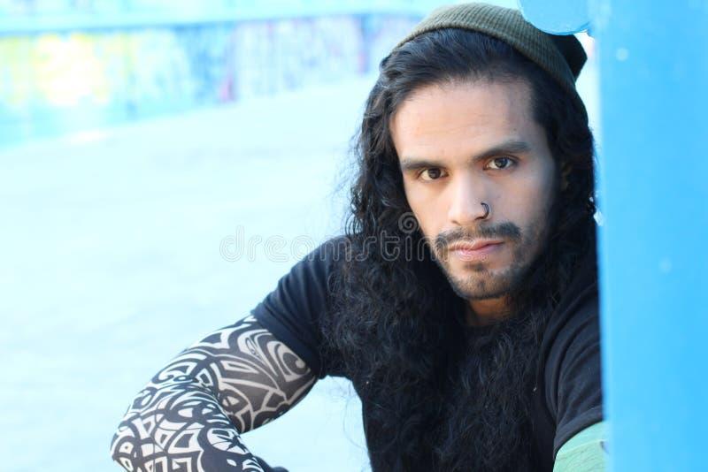 Hombre hispánico de mirada duro con el pelo y los tatuajes largos fotos de archivo