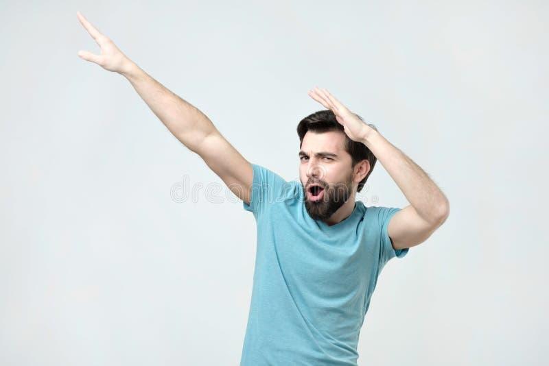 Hombre hispánico feliz joven en el baile azul de la camiseta foto de archivo