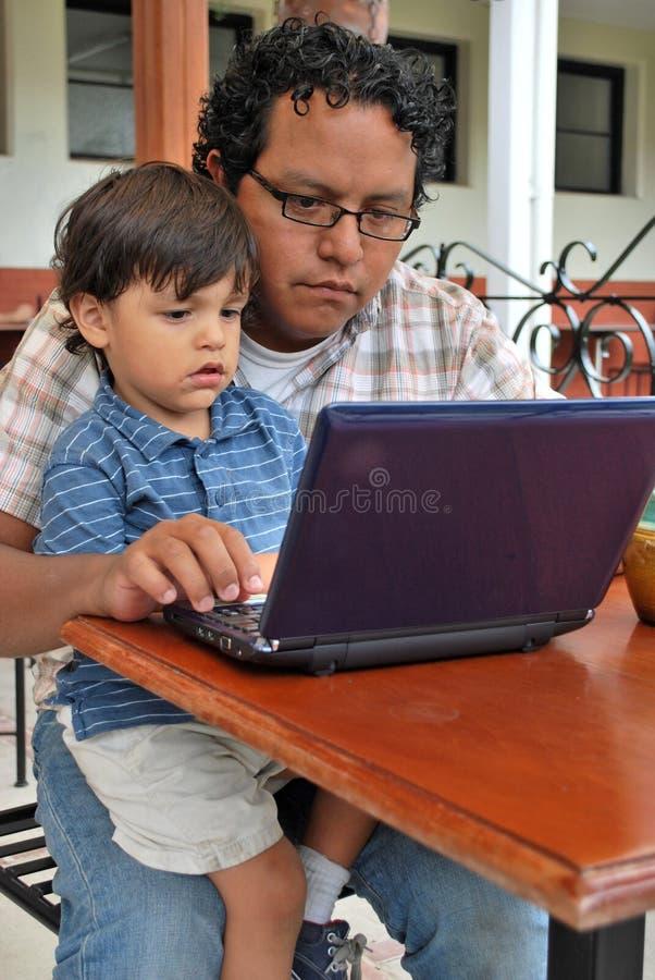 Hombre hispánico joven en un ordenador fotografía de archivo libre de regalías