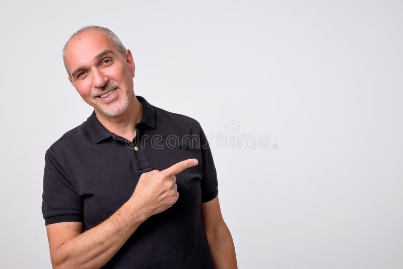 Hombre hispánico maduro que señala a un lado el espacio de la copia imagen de archivo