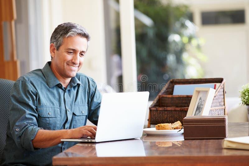 Hombre hispánico maduro que usa el ordenador portátil en el escritorio en casa imagenes de archivo
