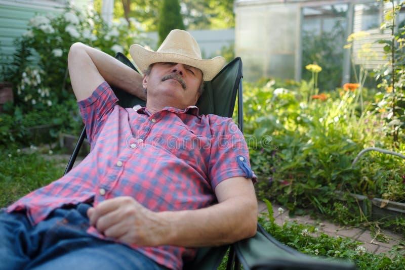 Hombre hispánico mayor en inclinarse que se sienta del sombrero detrás en silla que duerme en jardín de flores al aire libre del  imagenes de archivo