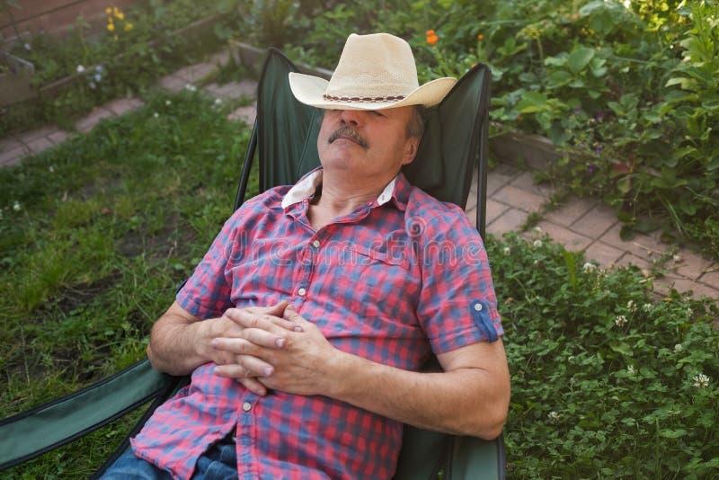 Hombre hispánico mayor en inclinarse que se sienta del sombrero detrás en silla que duerme en jardín de flores al aire libre del  foto de archivo libre de regalías
