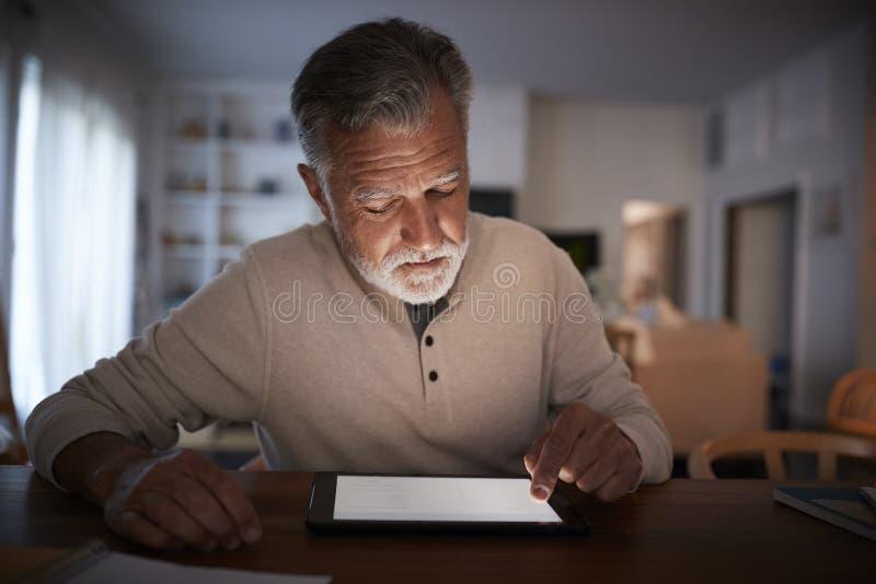 Hombre hispánico mayor que se sienta en una tabla usando una tableta en casa por la tarde, cierre para arriba imagen de archivo