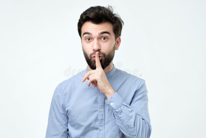 Hombre hispánico que coloca el finger en los labios como si decir, el shhhhh, sea reservado, silencio fotos de archivo