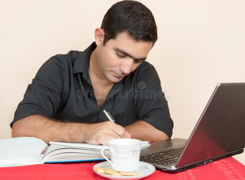 Hombre hispánico que estudia o que hace el trabajo de oficina en casa foto de archivo libre de regalías