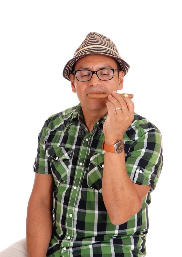 Hombre hispánico que goza de su cigarro foto de archivo