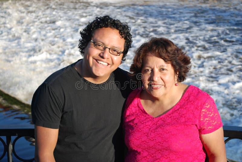 Hombre hispánico y su madre que sonríen por un río fotos de archivo libres de regalías