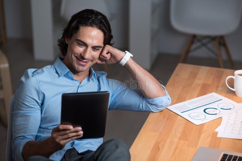 Hombre implicado joven hermoso que usa el ordenador portátil fotos de archivo libres de regalías