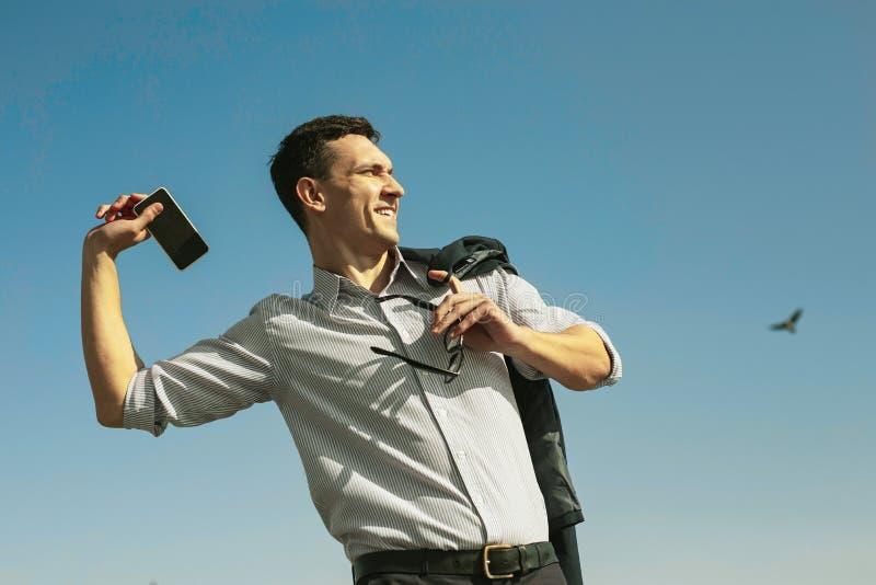 Hombre imponente feliz que lanza lejos su teléfono fotos de archivo libres de regalías