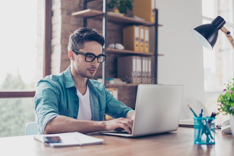 Hombre importado hermoso joven en sentarse de la camisa y de las gafas de los vaqueros foto de archivo libre de regalías