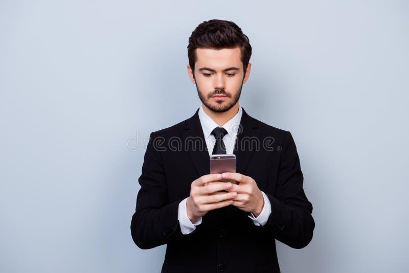 Hombre importado serio en el traje negro que sostiene smartphone y que mecanografía s foto de archivo