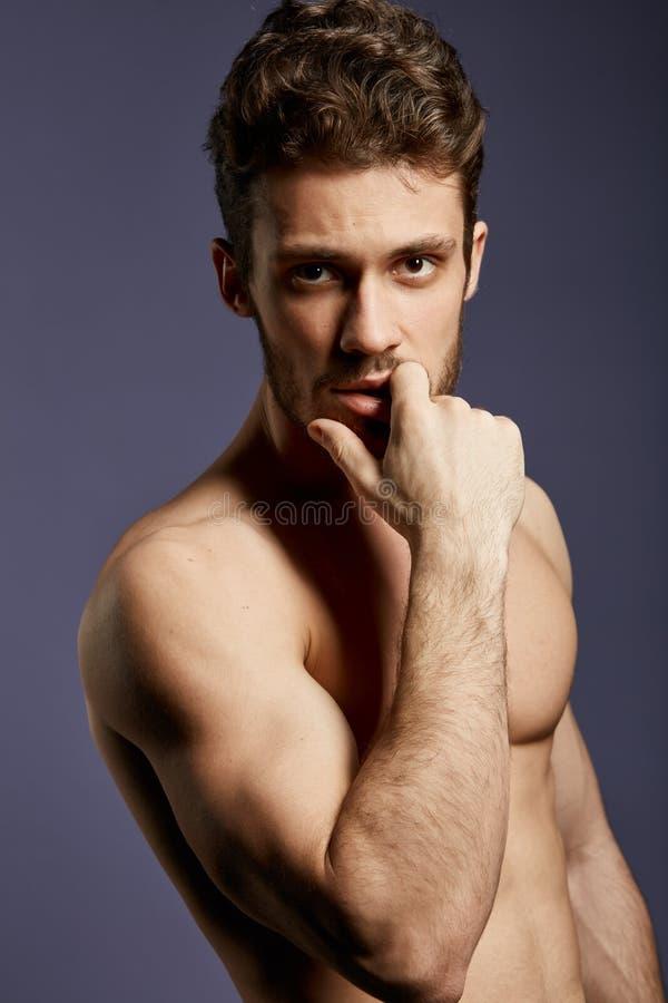 Hombre impresionante serio con un finger en su boca que mira la c?mara fotografía de archivo libre de regalías