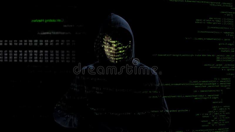 Hombre incógnito que mira los códigos y los números en la pantalla, ataque del pirata informático, crimen cibernético foto de archivo