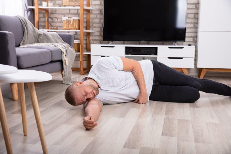 Hombre inconsciente que miente en piso fotos de archivo
