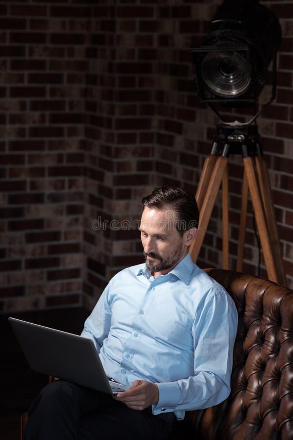 Hombre independiente atractivo que concentra en su trabajo imagen de archivo
