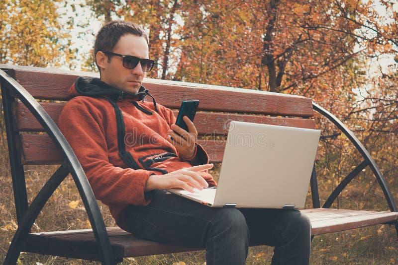 Hombre independiente joven que usa la PC del tel?fono m?vil y del ordenador port?til Estudiante del adolescente que habla en smar foto de archivo libre de regalías
