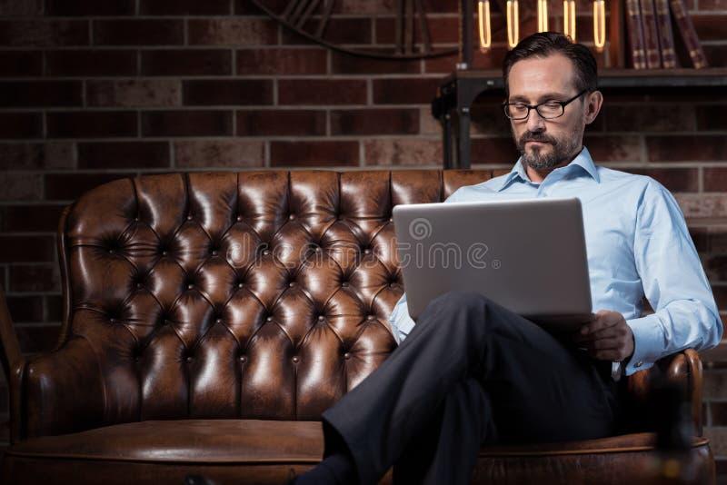 Hombre independiente serio que trabaja en el ordenador portátil imágenes de archivo libres de regalías