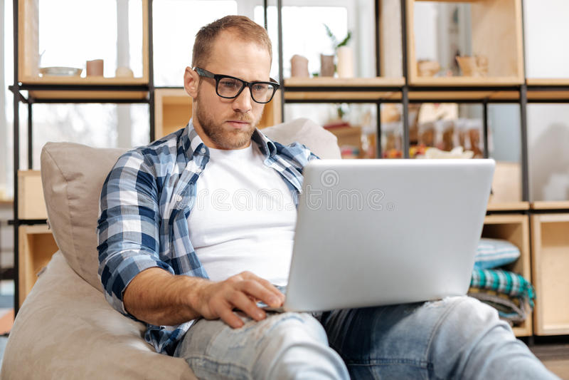 Hombre independiente serio que trabaja en un ordenador portátil imágenes de archivo libres de regalías