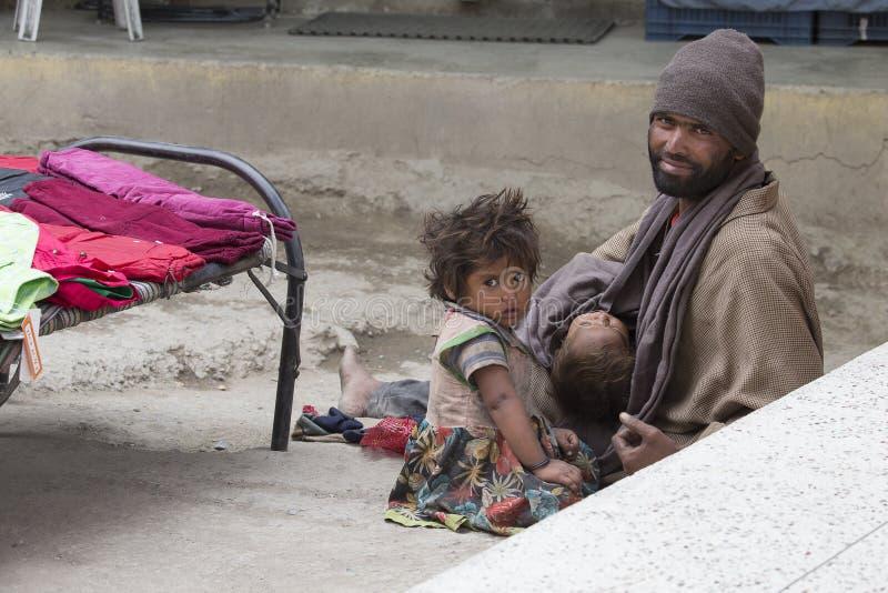 Hombre indio del mendigo con los niños en la calle en Leh, Ladakh La India fotografía de archivo