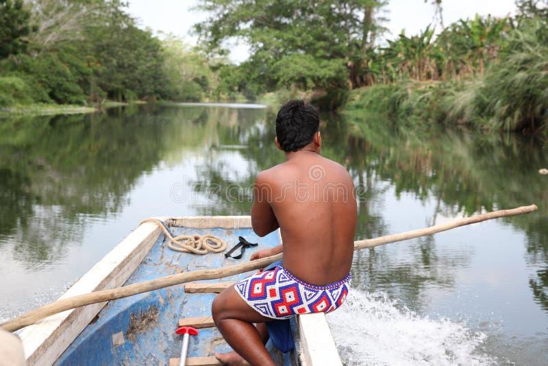 Hombre (indio) del nativo americano en un barco en un río Hombre indio foto de archivo