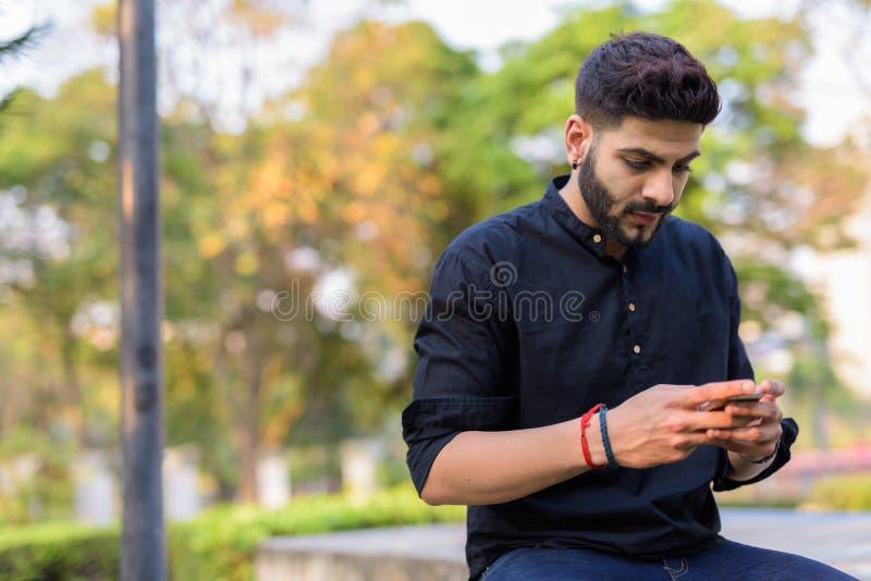 Hombre indio hermoso joven que usa el teléfono móvil mientras que se sienta en el co foto de archivo
