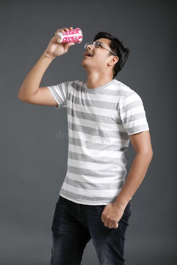 Hombre indio joven que bebe un agua foto de archivo libre de regalías