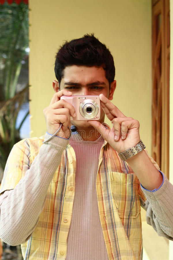 Hombre indio joven que toma la foto en cámaras digitales fotos de archivo libres de regalías