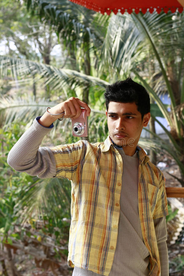 Hombre indio joven que toma la fotografía en cámara de P&S imagen de archivo
