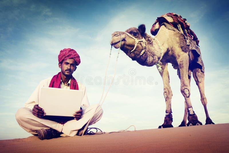 Hombre indio que usa concepto del desierto del ordenador portátil fotografía de archivo