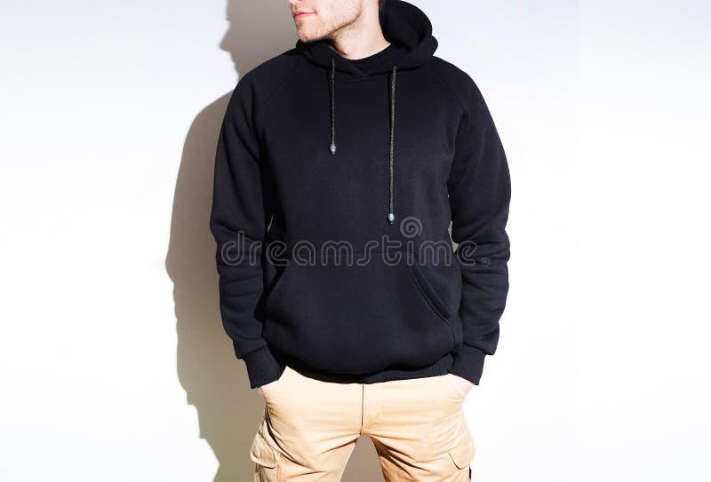 Hombre, individuo en la sudadera con capucha negra en blanco, camiseta, mofa para arriba aislada pl fotografía de archivo