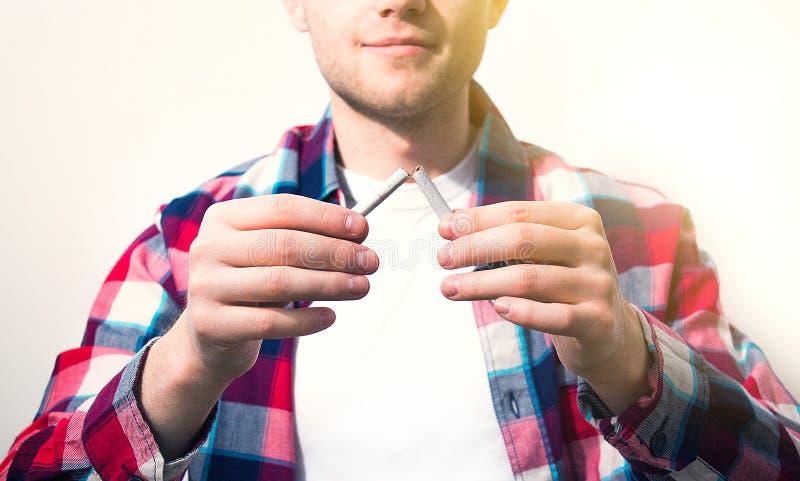 Hombre, individuo, inconformista que sostiene un cigarrillo quebrado, concepto de sano imagen de archivo libre de regalías