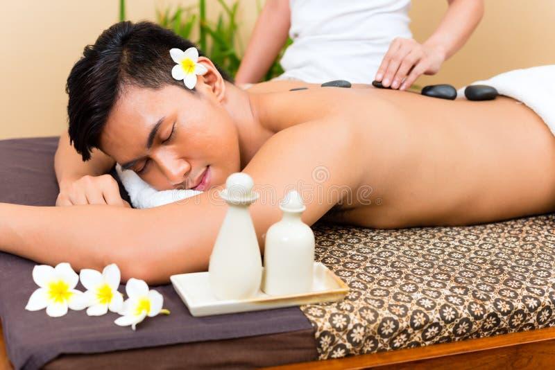 Hombre indonesio en el masaje de piedra caliente de la salud imagen de archivo