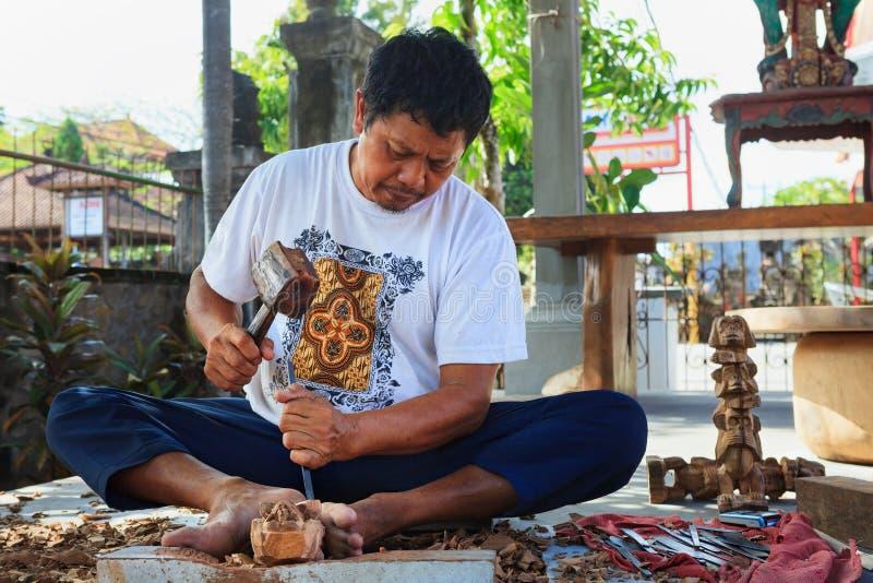 Hombre indonesio tallando a mano escultura decorativa de madera de teca fotografía de archivo libre de regalías