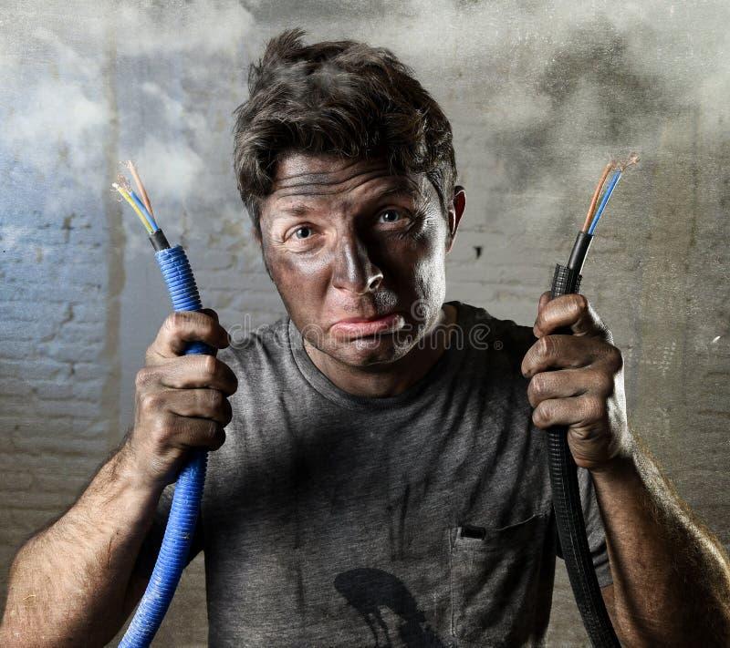 Hombre inexperimentado que se une al cable eléctrico que sufre accidente eléctrico con la cara quemada sucia en la expresión dive foto de archivo