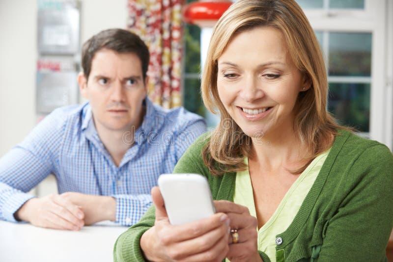 Hombre infeliz que se sienta en la tabla como textos del socio en el teléfono móvil imágenes de archivo libres de regalías