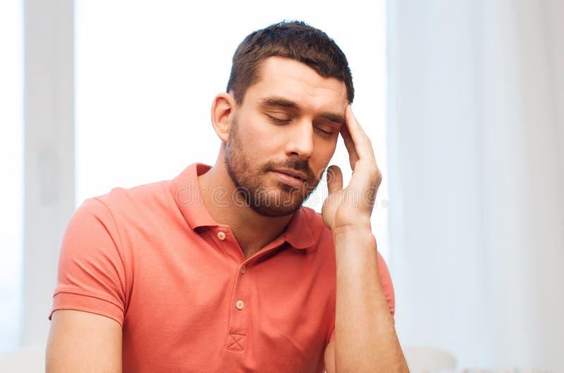 Hombre infeliz que sufre de dolor de cabeza en casa imágenes de archivo libres de regalías