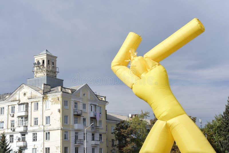 Hombre inflable amarillo en fondo del cielo azul imagenes de archivo