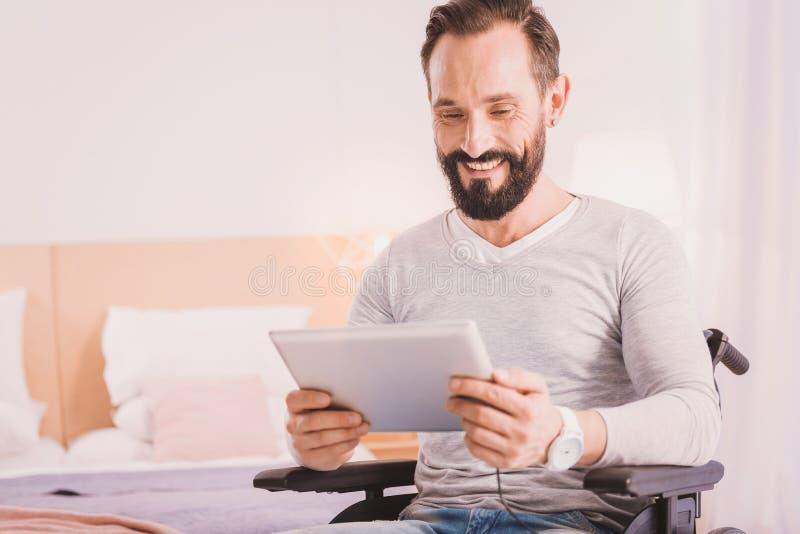 Hombre inhabilitado sonriente que usa una tableta en casa imagen de archivo libre de regalías