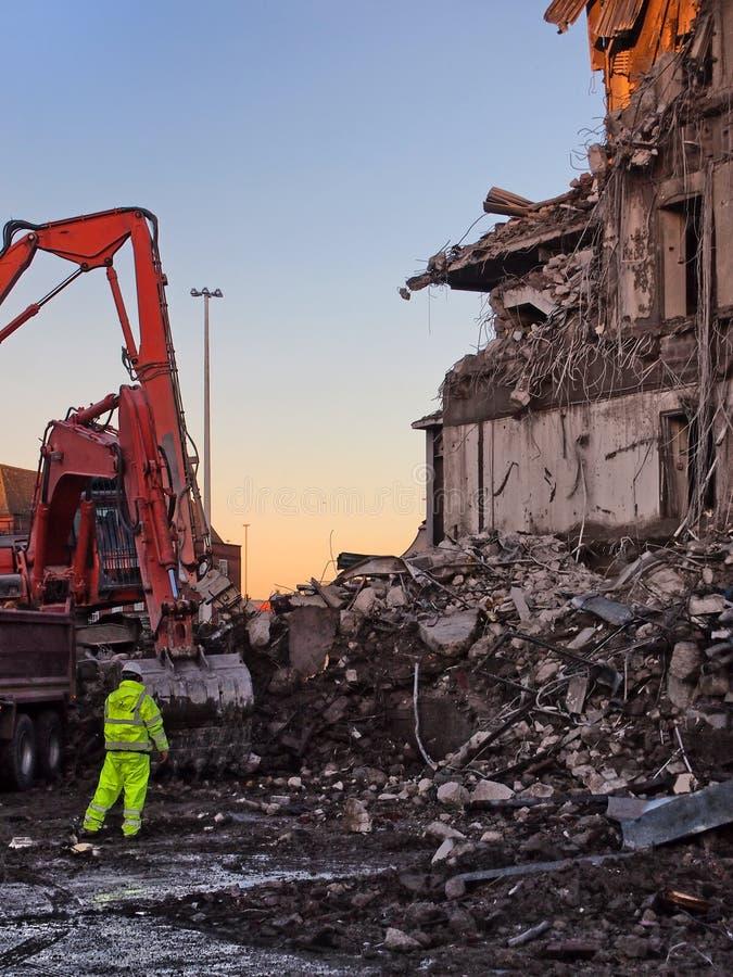 hombre inidentificable en la alta ropa de la visibilidad que trabaja delante de un excavador anaranjado en el sitio de demolición fotografía de archivo libre de regalías